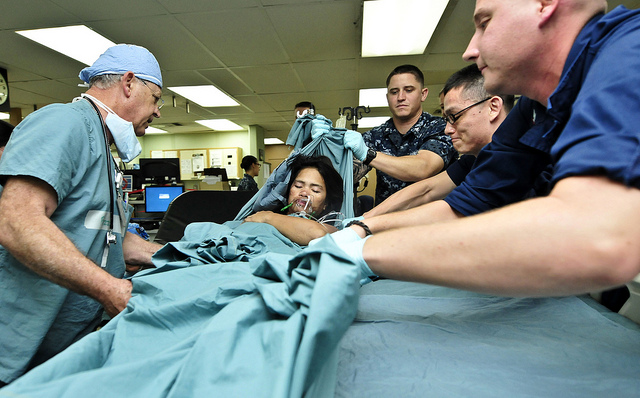 Service members from the U.S. Navy and Australian army help lift a Filipino women onto a bed in the intensive care unit.